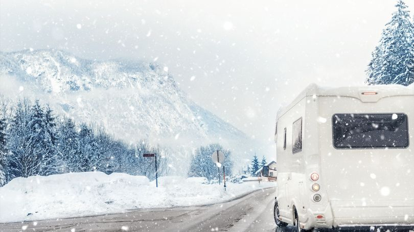 An RV driving on the road through the snowy mountains