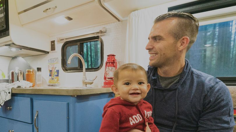 Smiling father and baby sitting inside RV.