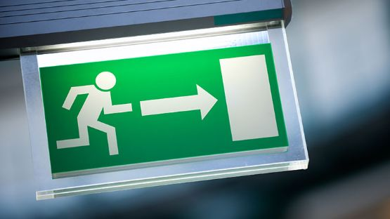 Close-up of a green emergency exit sign with an illustrated person running towards a door.