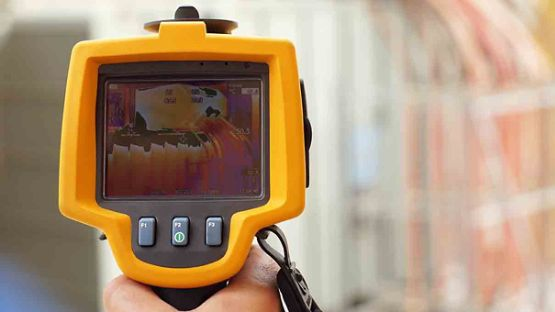 Technician using thermal imaging camera to check the temperature in a factory.