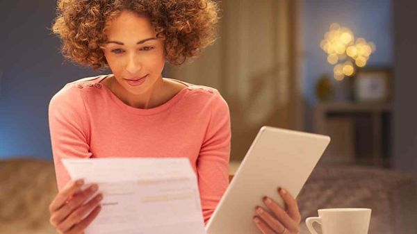 Woman reviewing expensive energy bills looking to save money.
