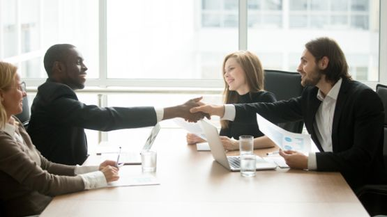 A claims service manager shaking hands with a corporate client.