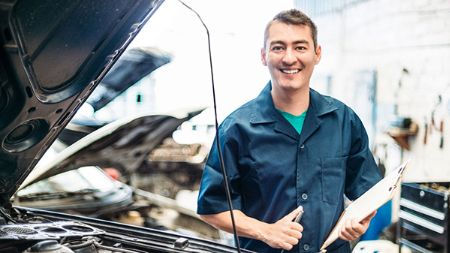 Smiling mechanic fixing car after claim.