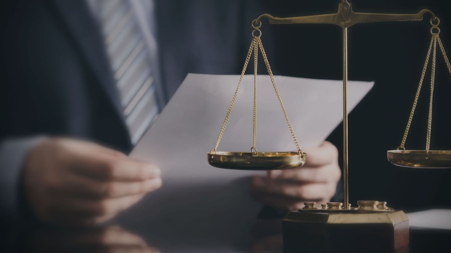 Close up of lawyer working in an office with scales of justice on the desk.