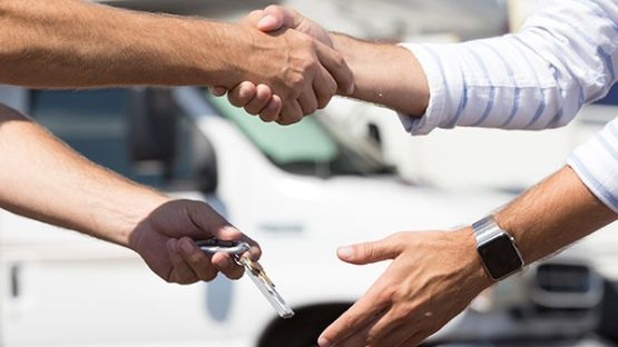 Close up of a handshake and key exchange with motor vehicles in the background.