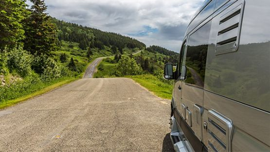 Motorhome on a dirt road with trees in the background.