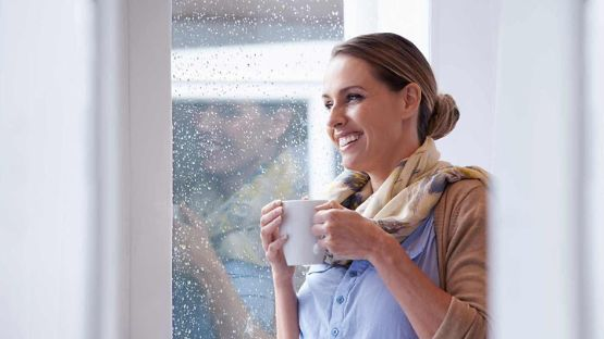 Woman holding a mug looking outside a window on a rainy day with a smile.