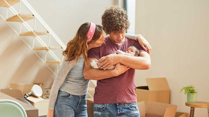 Couple with newborn in new house with boxes to unpack.