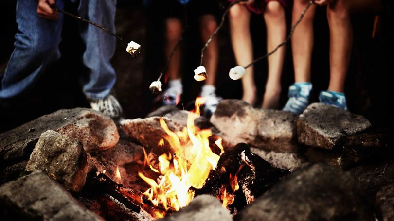 A group of people roasting marshmallows on a burning fire.