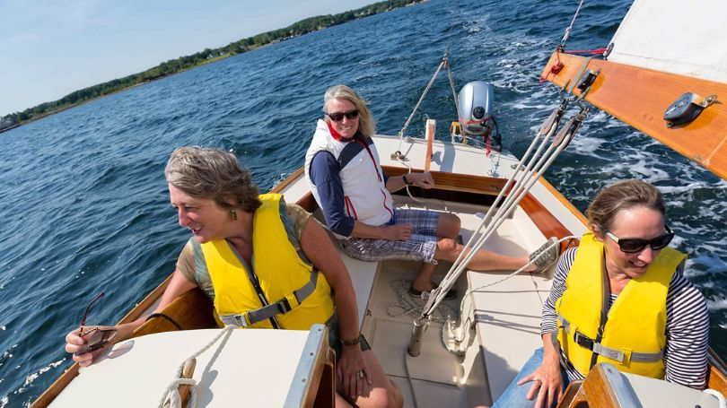 A group of women enjoying a beautiful day of sailing.