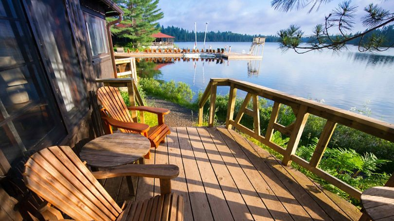 Muskoka chairs on a porch overlooking the lake.